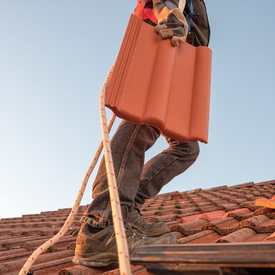 A Roofer Carrying a Tile.