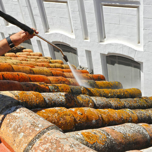 Hydro pressure washer washes terracotta clay tiles.