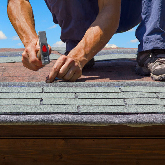 A crouching roofer hammering shingles.