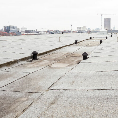 Commercial flat roof with cityscape in the background.