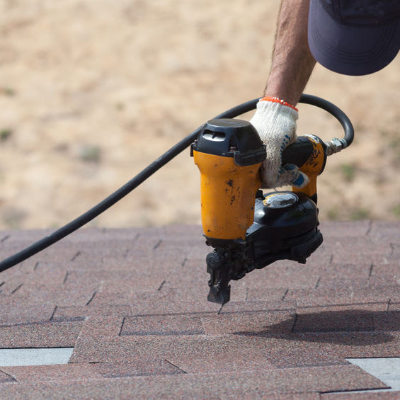 A Roofer Nailing Asphalt Shingles Down.