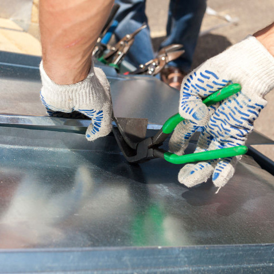 A Roofer Installing a Metal Panel.