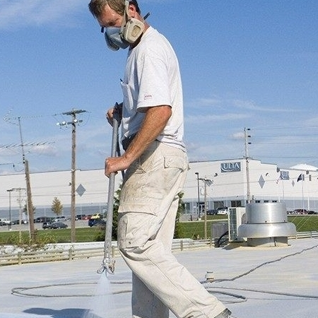 A Roofer Sprays on a Coating