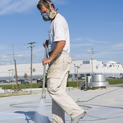 A Roofer Applies Flat Roof Restoration Coating.