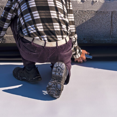 Roofer Installing Single Ply Roofing on Commercial Building