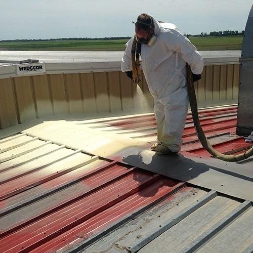A Roofer Sprays on a Polyurea Roof Coating.