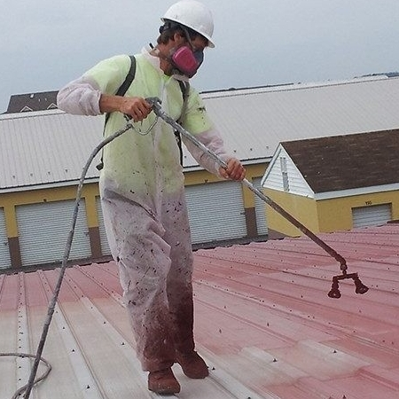 A Roofer Applies a Coating
