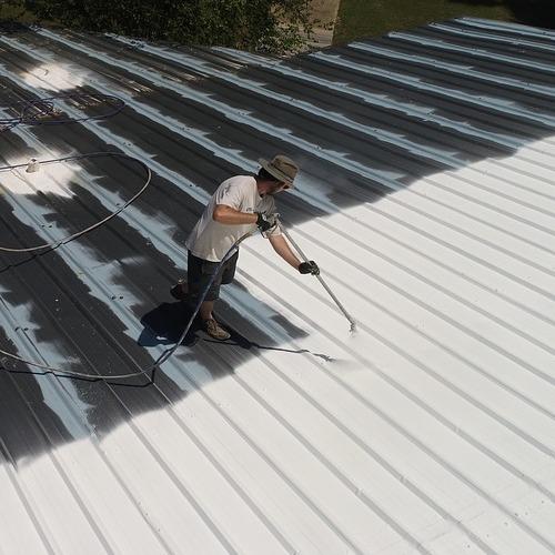 A Roofer Applying a Roof Restoration Coating.