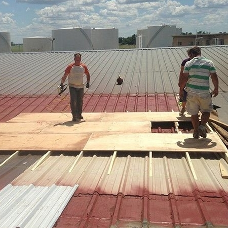Roofers Work on a Metal Building.