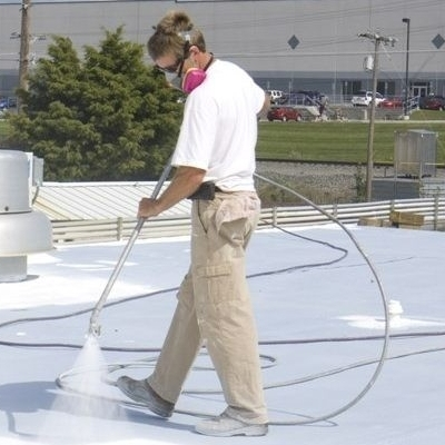 A Roofer Sprays on a Commercial Roof Coating.