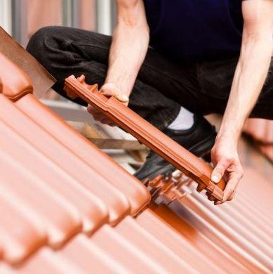 A Roofer Installs Tiles.